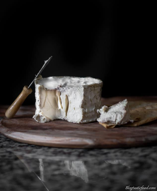 A photo of camembert cheese in a round wooden board with a small knife.