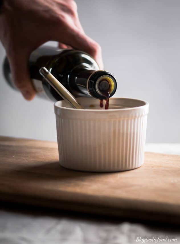 A photo of someone pouring balsamic vinegar in a ramekin.