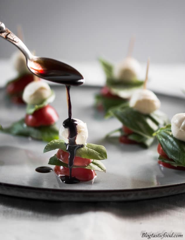 Mini caprese skewers with balsamic glaze being poured on top.