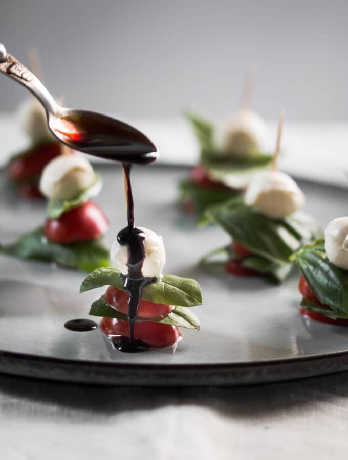 A photo of balsamic glaze being drizzled over mini caprese salad skewers.