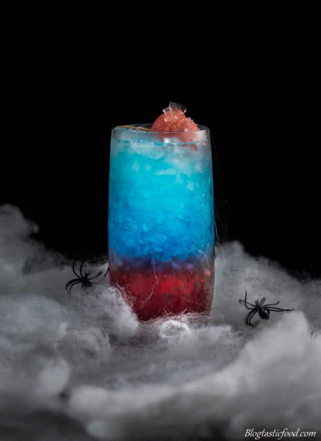 fake spiderwebs surrounding a layered red and blue spiderman themed cocktail.