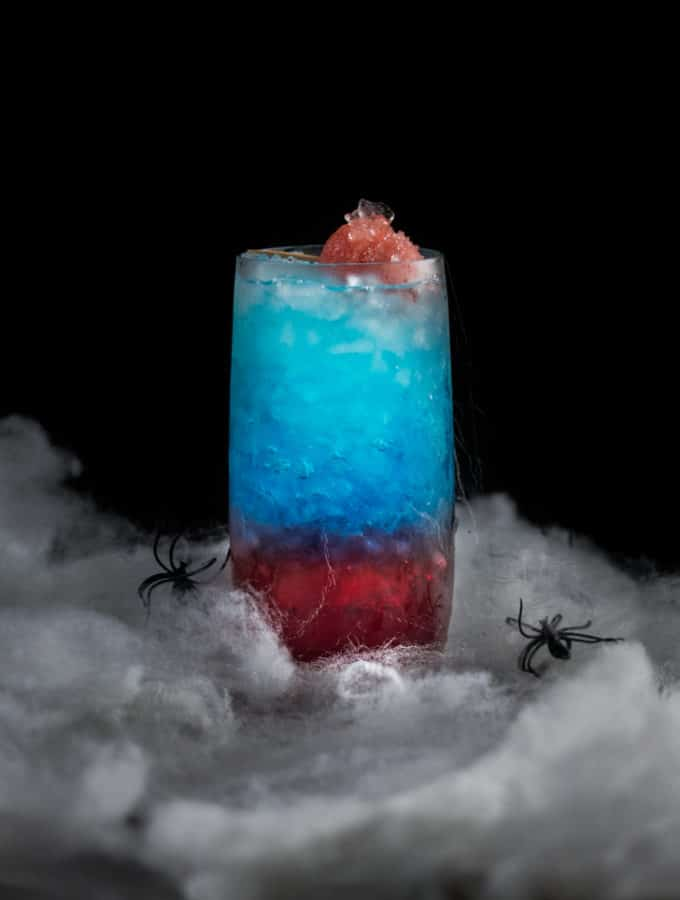 An eye level photo of a spiderman red and blue themed cocktail surrounded by webs.