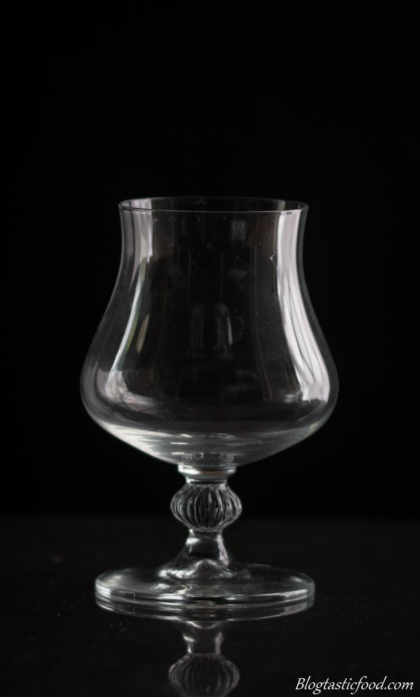 A dark, eye level photo of a dessert glass.