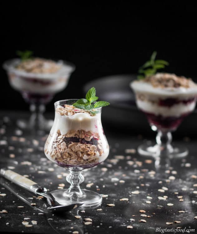 A dark moody photo of 3 yogurt parfaits with oats scattered around the surface.