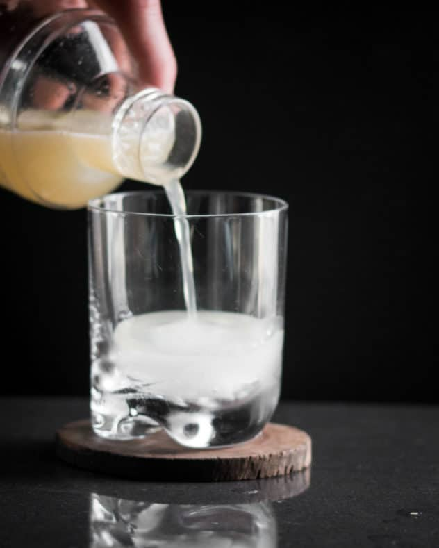 A photo of vegan whiskey sour being steained into a chilled glass.