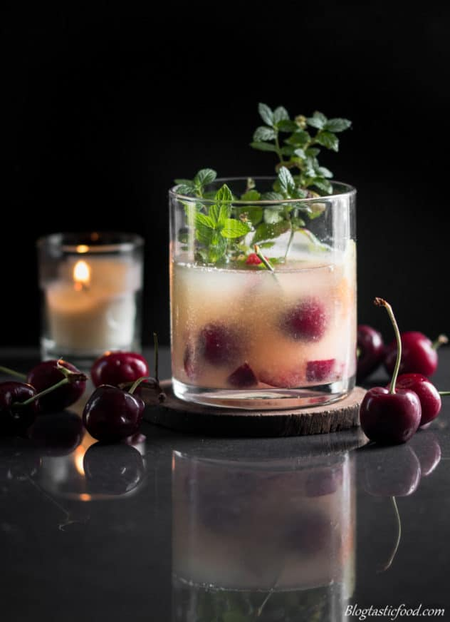 A photo of a whiskey sour cocktail served on a wooden coaster sourrounded by cherries.