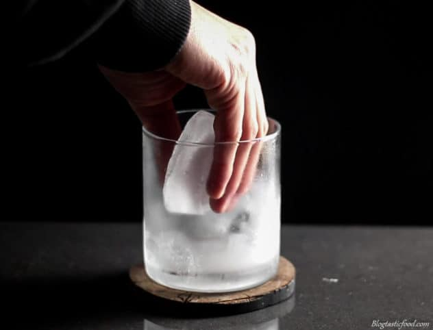 A photo of a giant ice cube being added to a chilled glass.