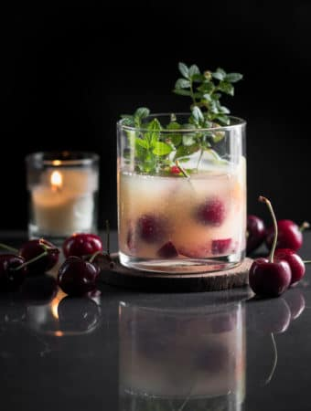An orange whiskey sour garnished with cherries and mint.
