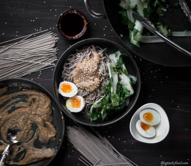A sobe noodle bowl, souurounded by soba noodles, peanut sauce in a pan, sauteed bok choy, medium boiled eggs and soy sauce.