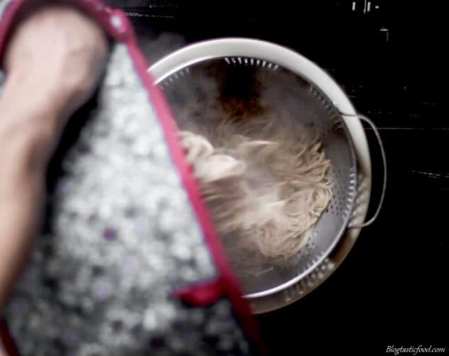 A photo of cooked soba noodles being drained in a colander.