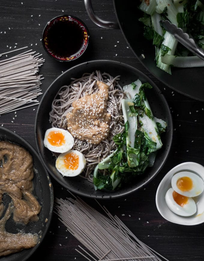 An overhead photo of soba noodles, peanut sauce, bok choy and a boiled egg in a bowl.