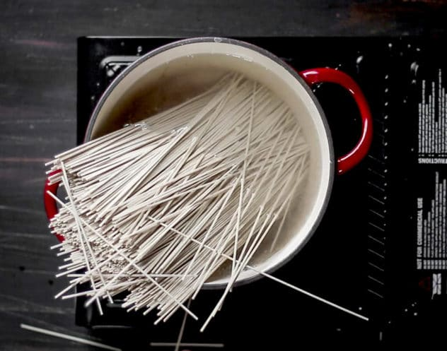A photo of soba noodles that have just been added to boiling water.