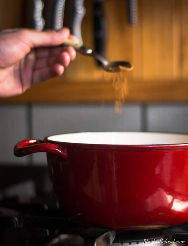A photo of cinnamon being added to a red pot on a stove.