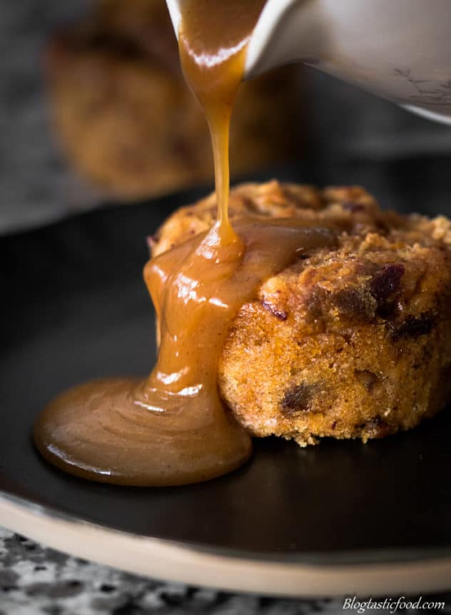 A photo of butterscotch sauce being poured over a mini steamed sticky date pudding.