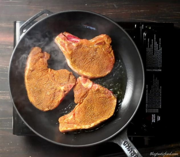 Spiced pork chops frying in ghee.