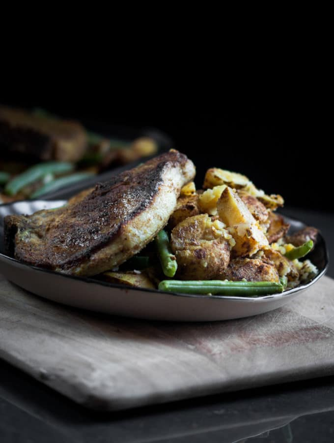 A baked curried sheet pan pork chop, potato and green bean recipe served on a ceramic plate.