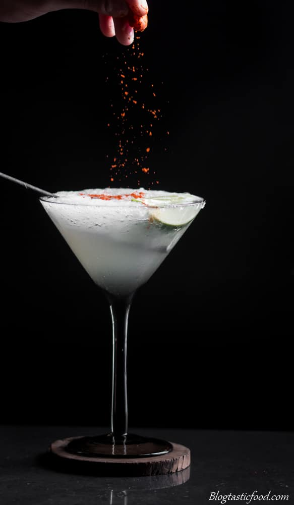 A photo of smoked paprika being sprinkled over a frozen margarita.