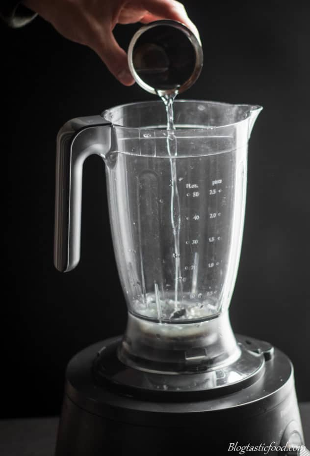 A photo of someone adding soda water to a blender.