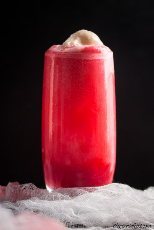 A photo of a blood orange cocktail, with a scoop of baileys ice-cream served on top.