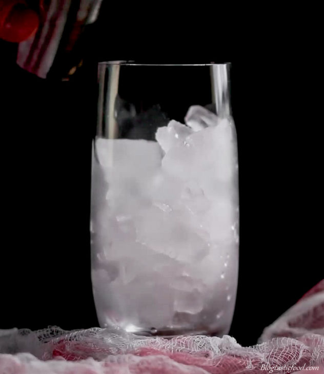 A photo of a tall glass filled with ice.