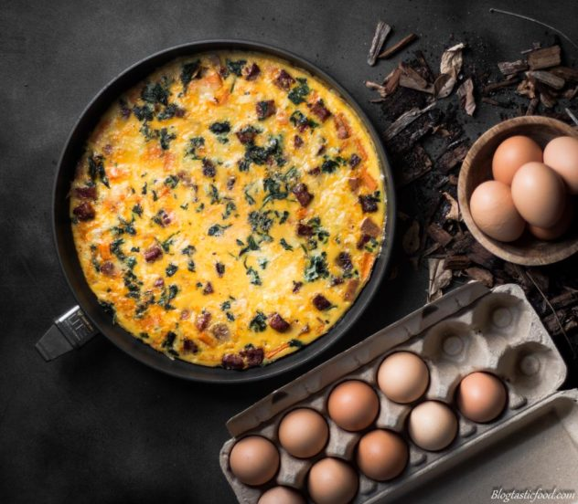 A photo of a frittata served in a non-stick pan, beside eggs.