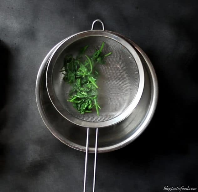 A photo of wilted spinach in a seive over a bowl.