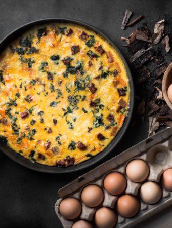 An overhead photo of a frittata in a pan next to a dozen eggs.
