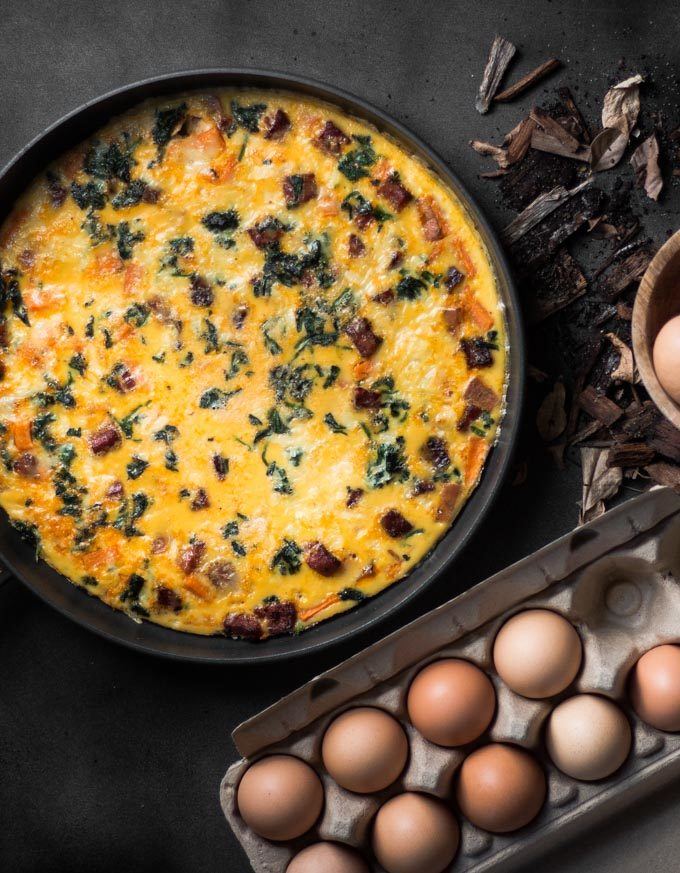 An overhead photo of a frittata in a pan next to a dozen eggs.