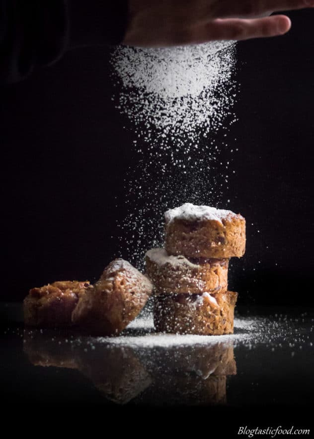A photo of icing sugar being dusted over mini sticky date puddings.