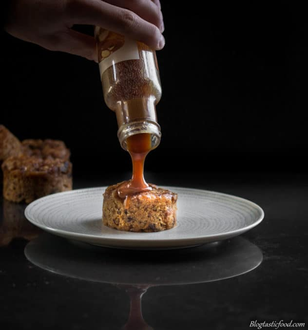 A photo of salted caramel sauce being poured over sticky date pudding on a plate.