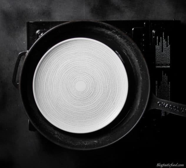 A white plate in a pan filled with hot water.