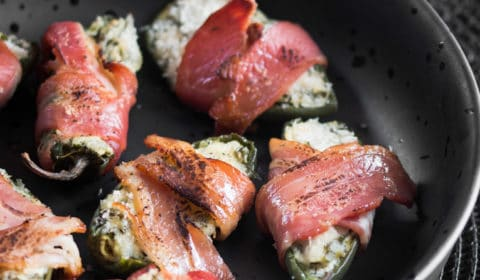 Cream cheese stuffped jalapenos wrapped in bacon, served in a fancy bowl.