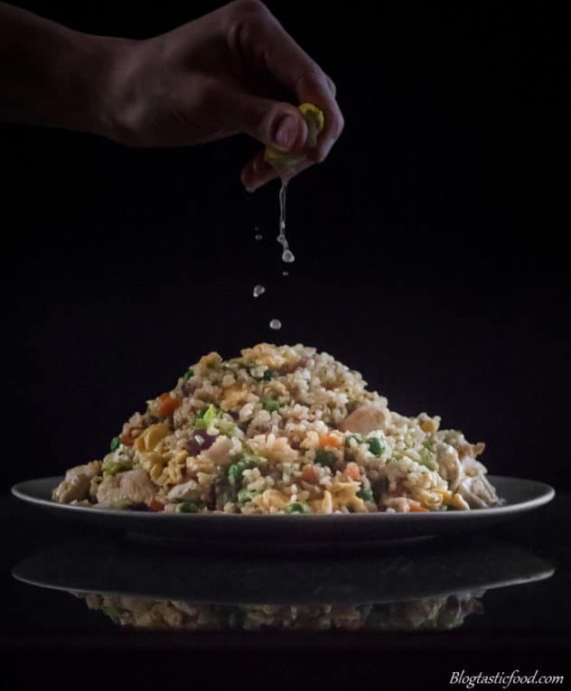 A pile of brown fried rice on a plate, with someone squeezing lime juice on top.