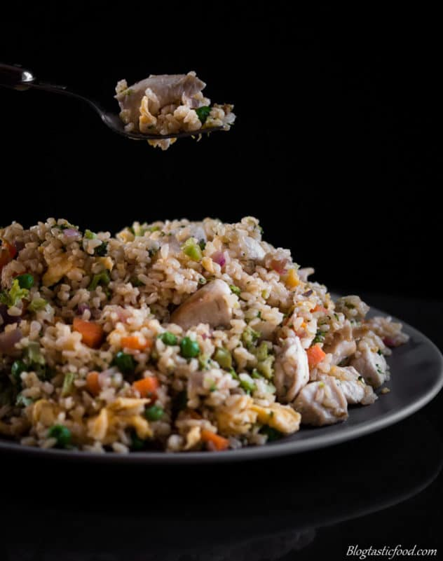 A photo of a fork holding some brown fried rice over a plate full of brown fried rice.