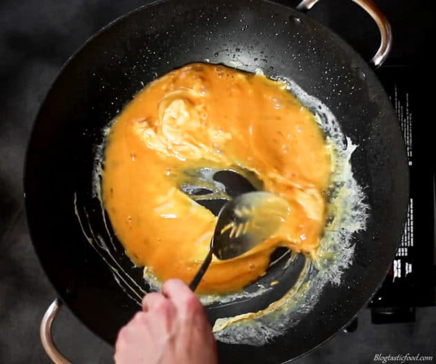 Beaten eggs being cooked in a hot wok.