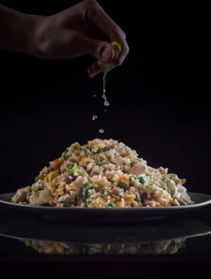 Lime juice being squeezed on top of a pile of brown fried rice.