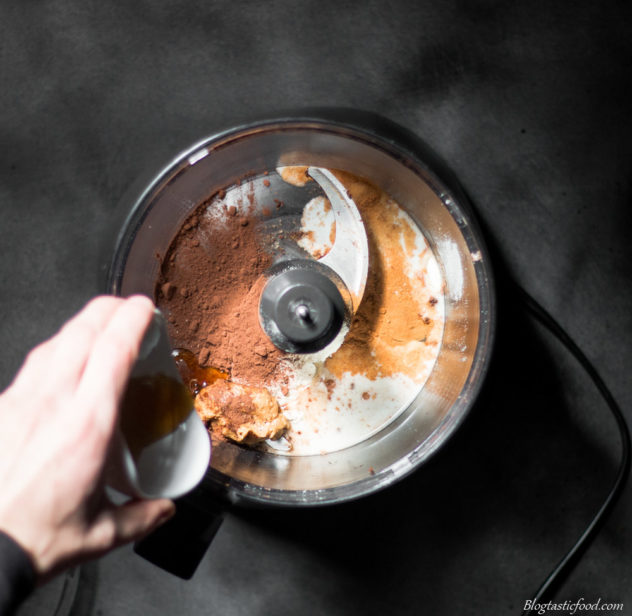 A photo of maple syrup being added to a food processor.