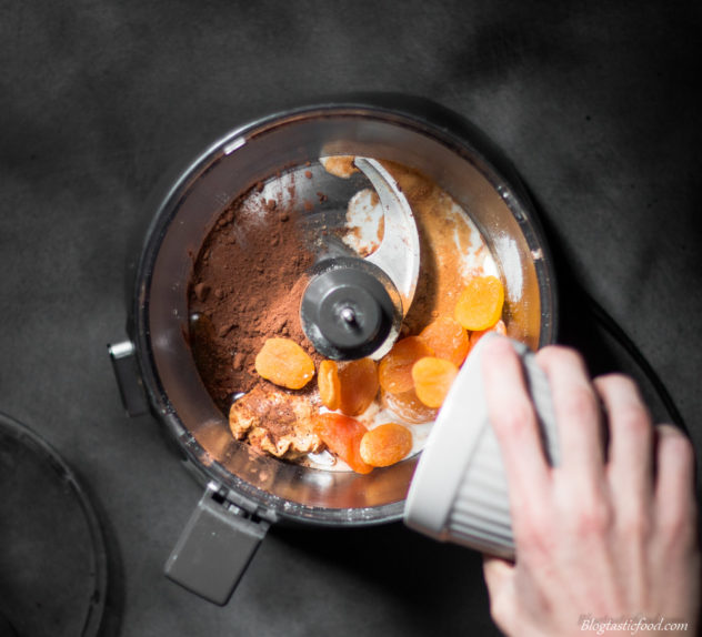 A photo of dried apricots being added to a food processor.