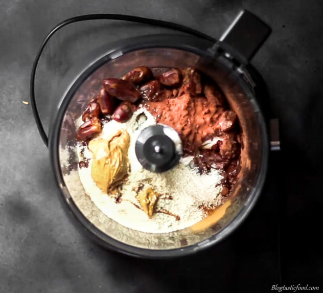 An overhead photo of peanut butter, almond meal, cocoa powder, dates, vanilla extract, almond milk, protein powder and ground cinnamon in a food processor.