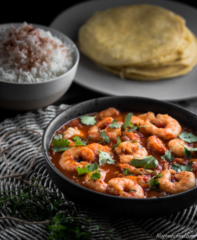Prawn Rougaille served in a black bowl with rice and dhal puri in the background.