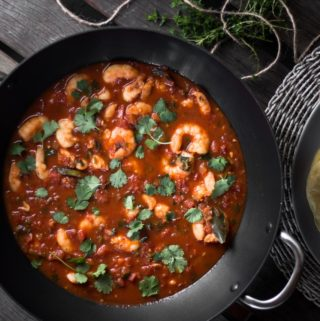 Prawn Rougaille served in a wok, garnished with parsley.