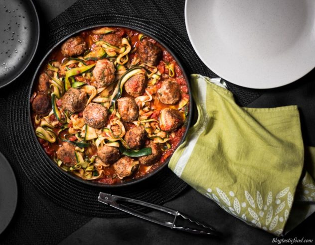 meatballs, tomato sauce and zoodles in a large pan with a cloth around the handle.