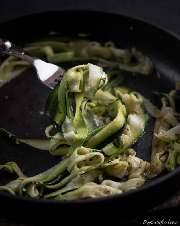 A photo of someone picking up pesto zoodles out of a pan with a fork.