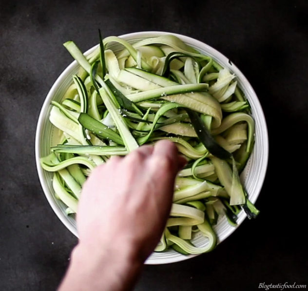An overhead photo of someone sprinkling salt over a bowl of zoodles.