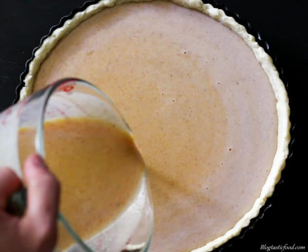 A photo of pumpkin pie filling being added to a patry case.
