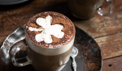 2 glass mugs of baileys irish coffee, one is served on a black plate and both are garnished with cocoa powder.