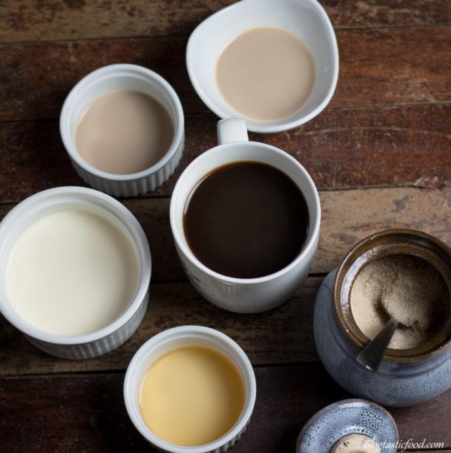 2 ramekins of baileys, 1 ramekin of cream, 1 ramekin of whiskey, 1 sugar bowl filled with brown sugar and 1 mug of coffee all on a wooden surface.