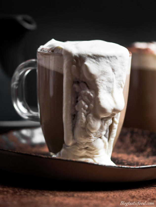An eye level photo of a glass mug of baileys Irish coffee with cream spilling over the edge.