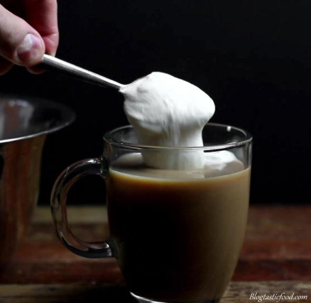 Semi whipped cream being spooned over baileys Irish coffee.