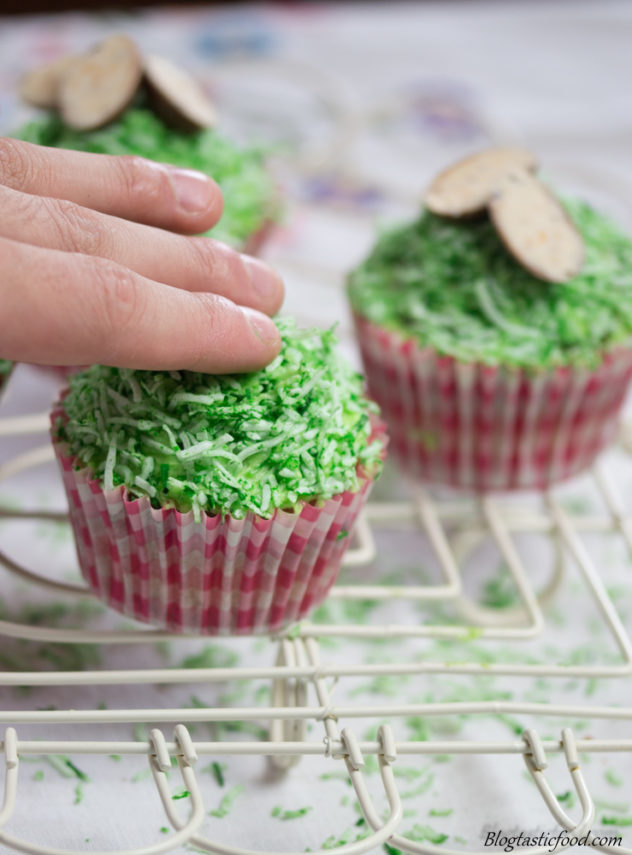 A photo of an imperfection on a cupcake being hidden with green shredded coconut.